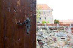 Botão de porta riscado vintage de uma porta de madeira marrom contra um panorama da cidade imagem de stock royalty free