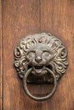 Botão de porta de uma construção histórica velha na forma de um leão feito do ferro fotografia de stock