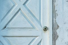 Botão de prata na porta de madeira branca velha com muro de cimento imagem de stock