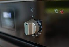 Botão do regulamento de temperatura no painel de controle do fogão imagem de stock
