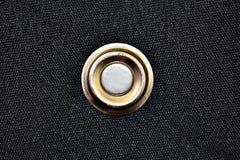 Botão dourado na matéria têxtil preta foto de stock royalty free