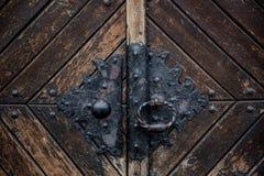 Botão preto velho do metal de uma porta velha no castelo medieval envelhecido fotos de stock