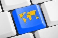 Botón azul del mapa del mundo en el teclado Fotos de archivo libres de regalías