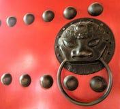 Botón chino del león del bronz en puertas rojas de la puerta Fotos de archivo