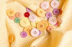 Botón colorido del paño en fondo del mantel Imagenes de archivo