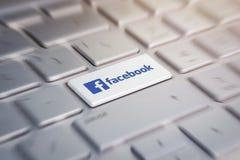 Botón con el facebook del logotipo de la compañía en el teclado gris de un ordenador portátil moderno imagenes de archivo