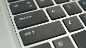 Botón de bloq mayús femenino del presionado a mano en el teclado para hacer el capital de las letras que mecanografía metrajes
