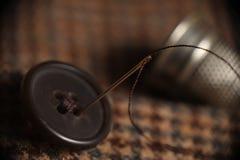 Botón de costura de la aguja en una capa del pío Imagenes de archivo