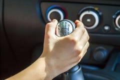 Botón de desplazamiento del cambio de marcha de la mano del conductor manualmente, foco selectivo imagen de archivo