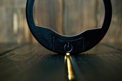 Botón de encendido redondo negro en fondo casero de madera Contraluz llevado La geometría es un círculo dentro de un rectángulo fotos de archivo