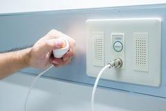Botón de la llamada de la enfermera de la emergencia del presionado a mano Imagenes de archivo