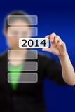 Botón de la pantalla con el número 2014 a mano. Foto de archivo libre de regalías
