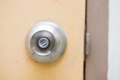 Botón de puerta de acero en la puerta amarilla Foto de archivo