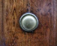 Botón de puerta de cobre amarillo en la puerta de madera vieja Foto de archivo
