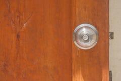 Botón de puerta del metal en puerta abierta de madera Foco suave Imagen de archivo