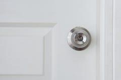 Botón de puerta viejo en la puerta blanca Foto de archivo