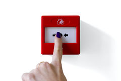 Botón del disparador la alarma de incendio que es presionado por el dedo Fotos de archivo libres de regalías