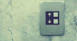 botón del elevador en las paredes de la piedra caliza Foto de archivo