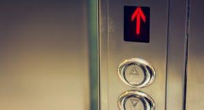 Botón del elevador hacia arriba y hacia abajo y una pantalla que muestra una flecha roja Fotografía de archivo libre de regalías