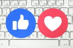 Botón del gusto y del amor de Facebook de las reacciones comprensivas de Emoji puestas en el teclado blanco imagen de archivo libre de regalías