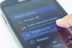 Botón del modo del vuelo de la prensa del finger en smartphone imagen de archivo