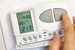 Botón del presionado a mano en el termóstato digital Foto de archivo libre de regalías