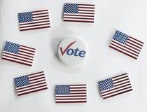 Botón del voto rodeado por las banderas de los E.E.U.U. Imagenes de archivo