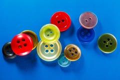 Botões coloridos no fundo azul Imagem de Stock