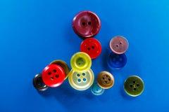 Botões coloridos no fundo azul Foto de Stock