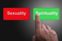Bot?es com espiritualidade e sexualidade e o dedo escritos apontar, em um fundo cinzento do inclina??o imagens de stock