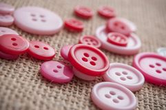botões cor-de-rosa da costura no fundo da textura da juta Imagem de Stock