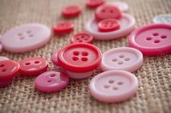 botões cor-de-rosa da costura no fundo da textura da juta Fotos de Stock