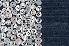 Botões da madrepérola na sarja de Nimes azul fotos de stock