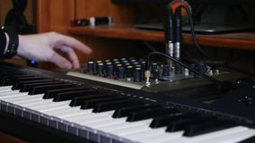 Botões de gerencio da mão do coordenador sadio na placa e no soundboard de mistura ao misturar e ao dominar a trilha da música no vídeos de arquivo