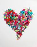 Botões dispersados na forma do coração Fotos de Stock Royalty Free