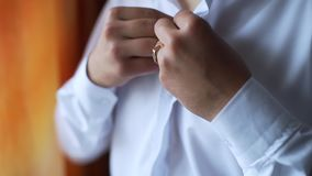 Botões do noivo acima de sua camisa branca filme