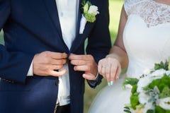 Botões do noivo dos jovens no revestimento Noiva que está próximo Imagem de Stock Royalty Free