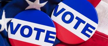 Botões do voto em um fundo da bandeira americana Fotografia de Stock Royalty Free
