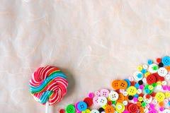 Botões e pirulito coloridos do redemoinho no papel cor-de-rosa da amoreira foto de stock royalty free