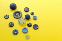 Botões plásticos azuis no fundo de papel amarelo Imagem de Stock Royalty Free