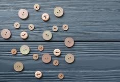 Botões plásticos cor-de-rosa no fundo de madeira cinzento Imagem de Stock