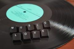 Botões que rotulam o amor da música sobre um registro de vinil preto fotografia de stock