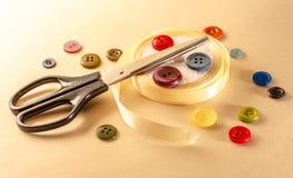 Botões, tesouras e rolo coloridos da fita Fotos de Stock Royalty Free