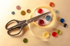 Botões, tesouras e rolo coloridos da fita Fotografia de Stock Royalty Free