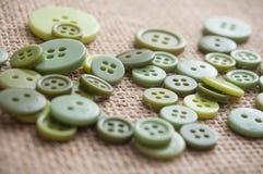 botões verdes da costura no fundo da textura da juta Imagens de Stock Royalty Free