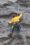 Bot Climbing Rock Wall. Young Boy Climbing Rock Wall Royalty Free Stock Images