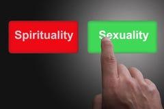 Bot?es com espiritualidade e sexualidade e o dedo escritos apontar, em um fundo cinzento do inclina??o foto de stock