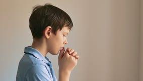 Bot tiener die op zwarte achtergrond bidden stock video