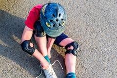 Bota adolescente del cambio del muchacho de la opinión del día en el estacionamiento del coche Foto de archivo libre de regalías
