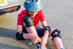 Bota adolescente del cambio del muchacho de la opinión del día en el estacionamiento del coche Imagen de archivo libre de regalías